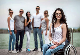 Disabled girl in wheelchair with friends