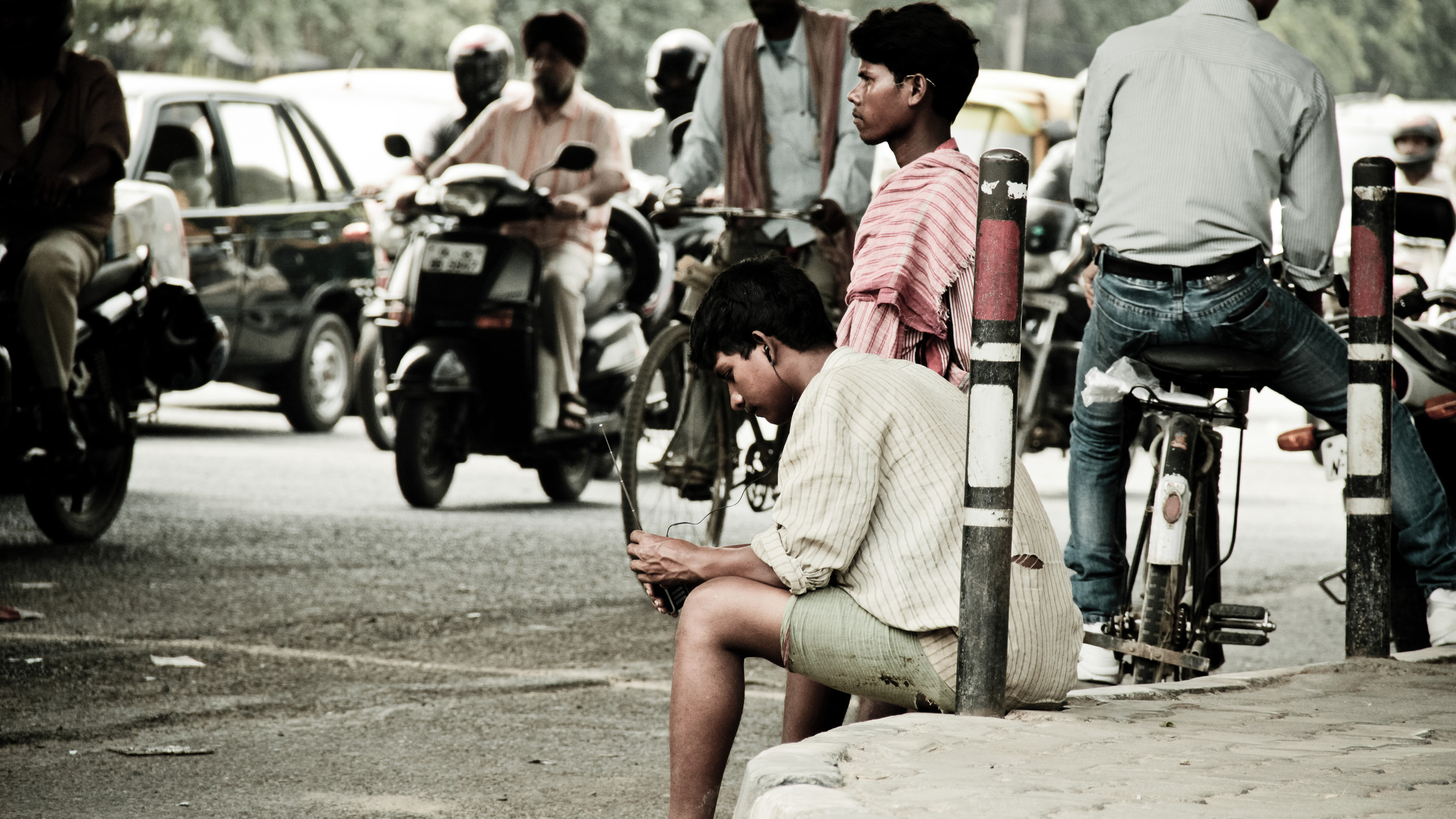 Young migrant boys wait for their contractor who has hired them for the day. Daily-wage labourers usually stand at busy intersections or chowks where contractors and employers pick them up in the morning