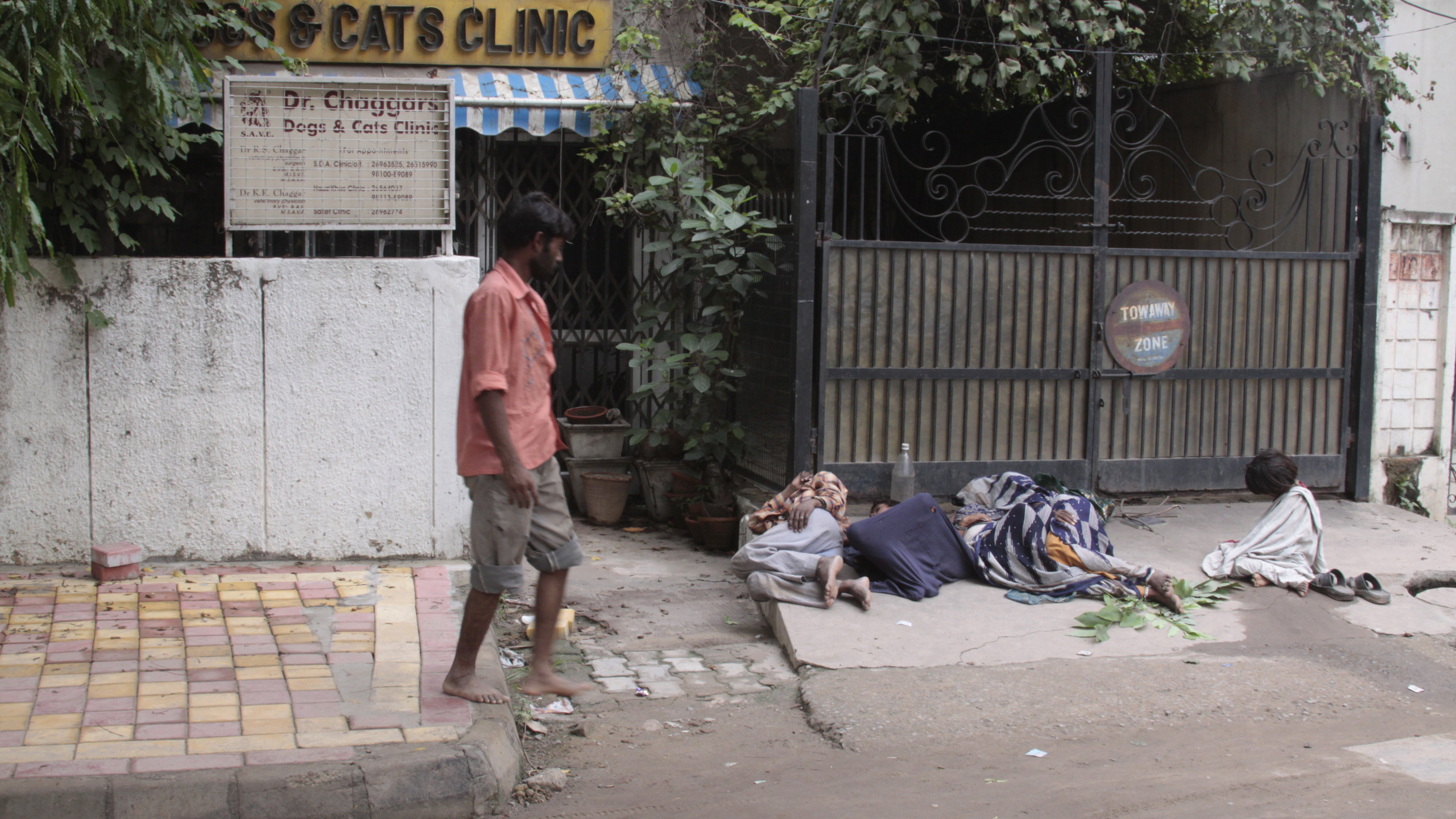 A passerby stares at a migrant worker family sleeping outside a veterinary clinic
