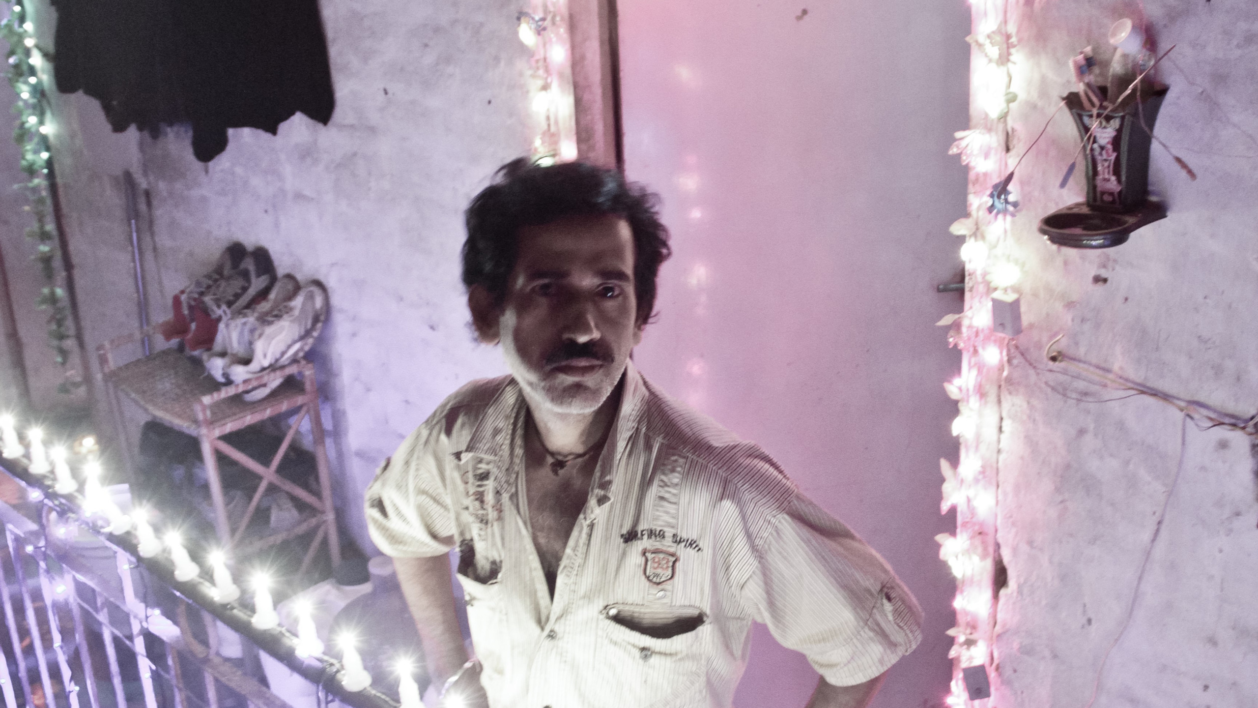 An electrician outside his one-room tenement that is decorated for Diwali, a major Hindu festival in India