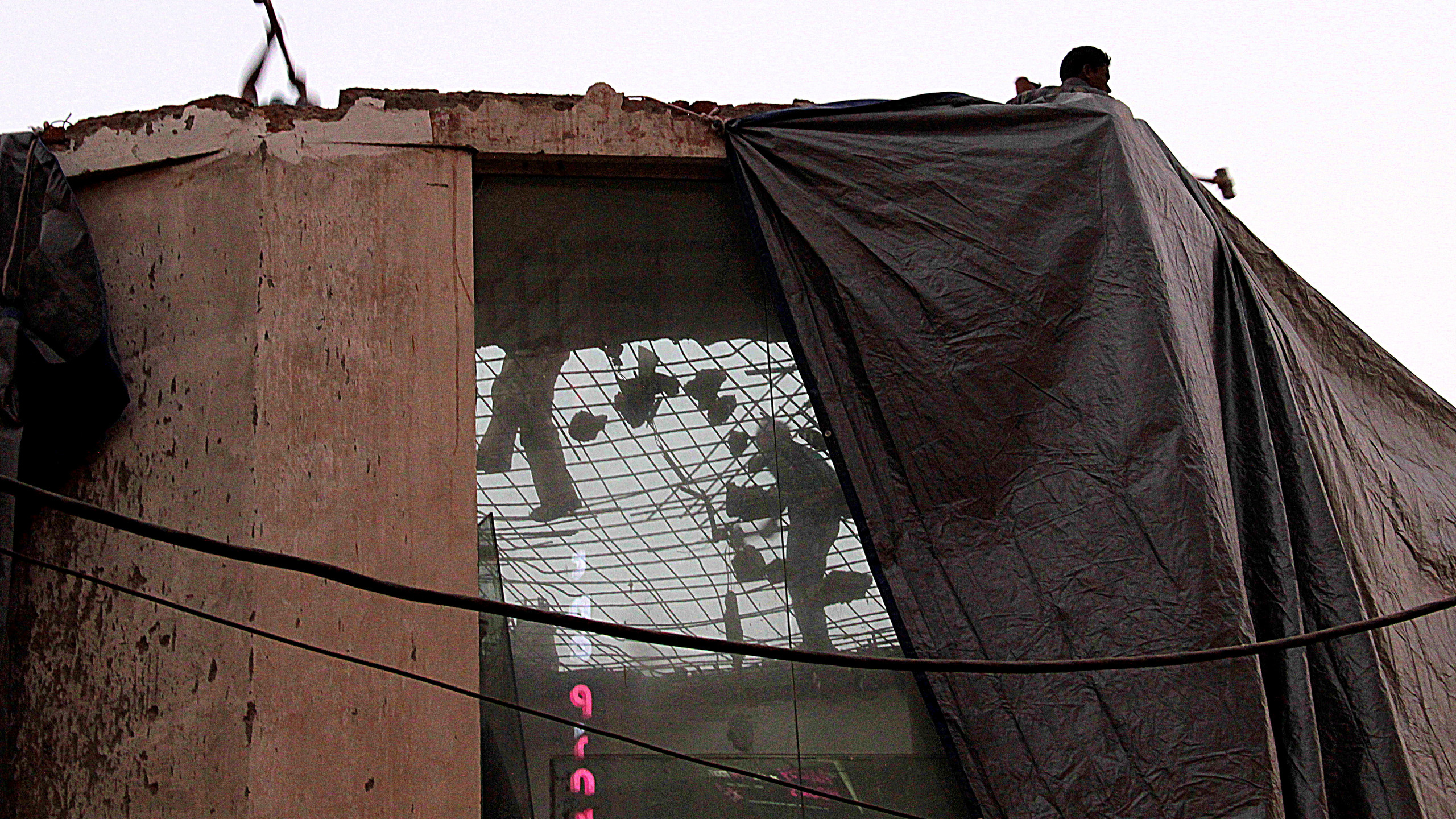 Workers break down an old home as a dust storm approaches South Delhi. The new building will house a café and a French bar