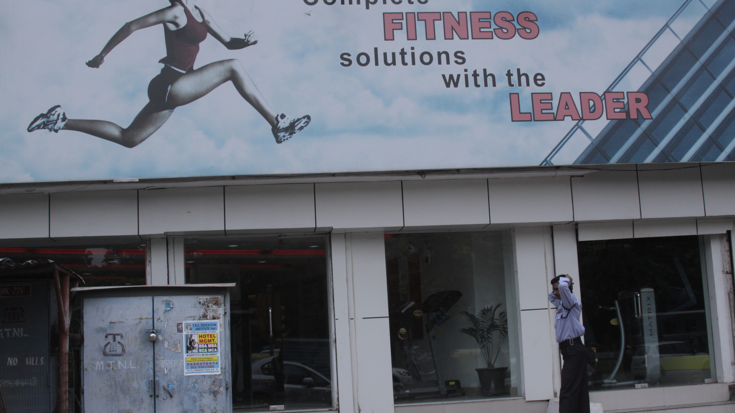 A security guard stretches outside the gym and fitness store where he is employed. A guard's shift is usually 12 hours or more