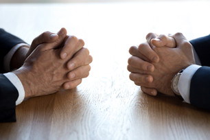 Clasped hands of two business men negoti