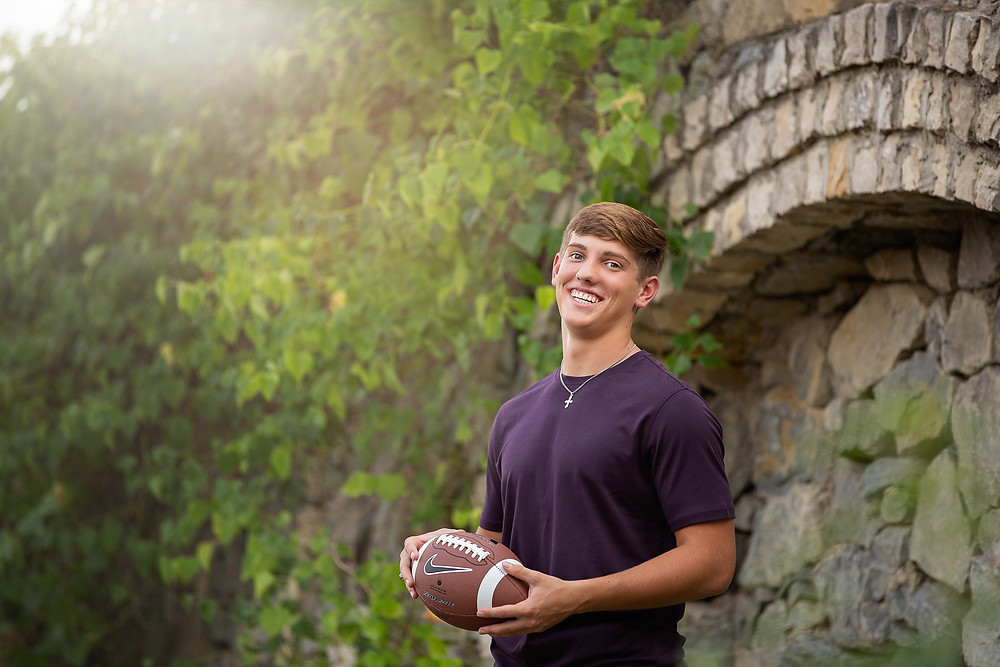 senior boy poses with football