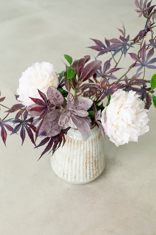 Faux peonies in stone pot