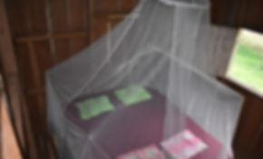 Schlafzimmer mit Moskitonetzen auf der Tamandu Lodge