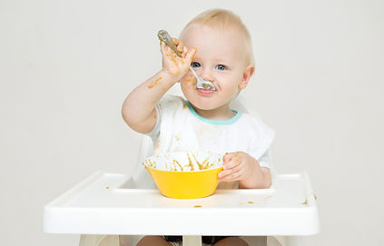 A baby eating food from a bowl against a