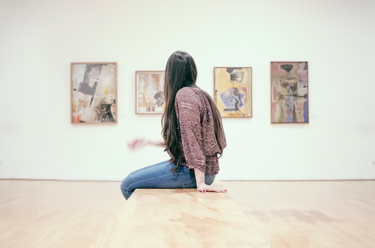 Person with long straight hair and chequered blouse sits on a wooden chair at the middle of an art gallery. On the wall behind them, four paintings.