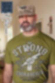 Be-Strong-and-Courageous-t-shirt-mockup-featuring-an-army-man-in-uniform-inside-his-house