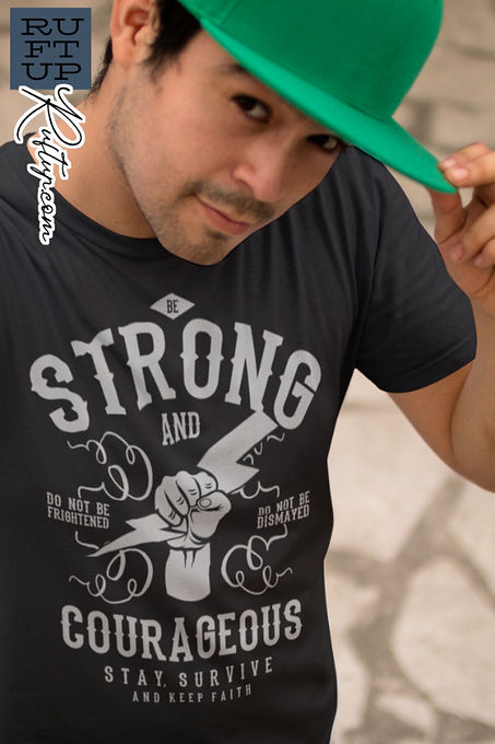 Young Man wearing a green baseball cap and sporting the Ruftup Be Strong Design on the front of his black t-shirt