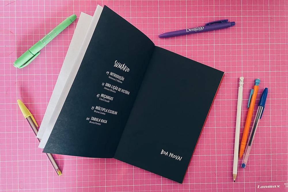 """Foto do sumário do livro """"A matemática das relações humanas"""". Em volta do livro há canetas, lápis e lapiseiras."""