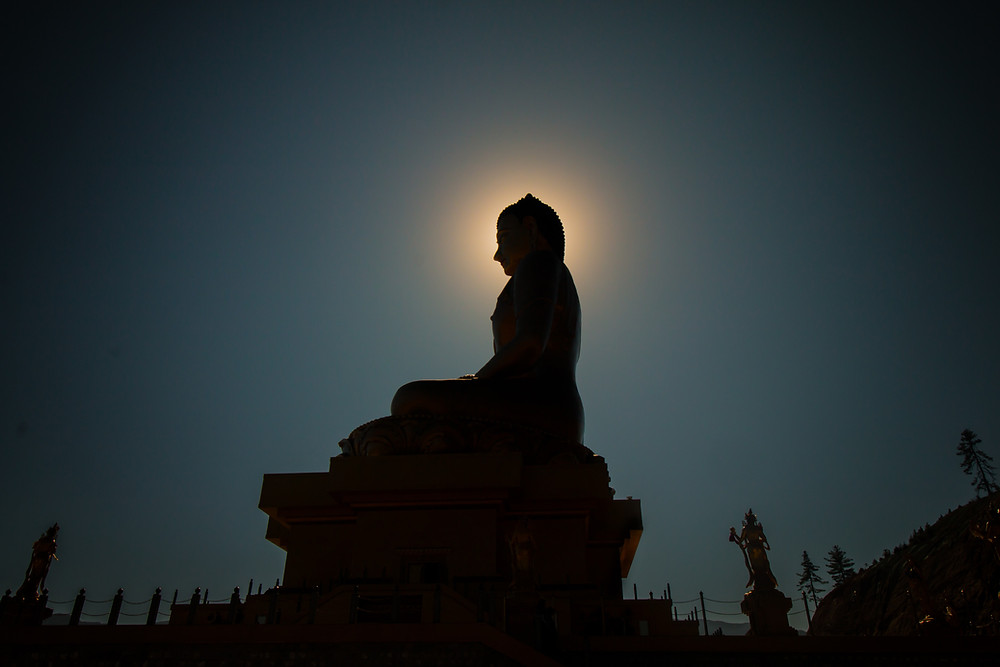 Silhouette of a Statue of the Buddha with the moon framing the head