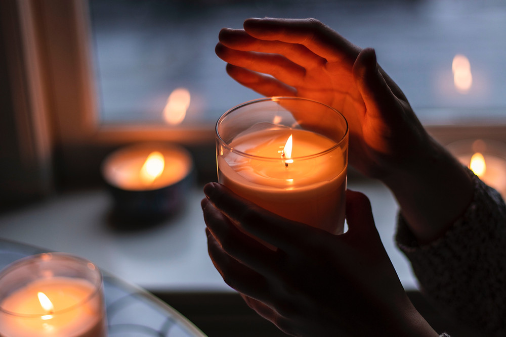 A hand being held over a candle flame