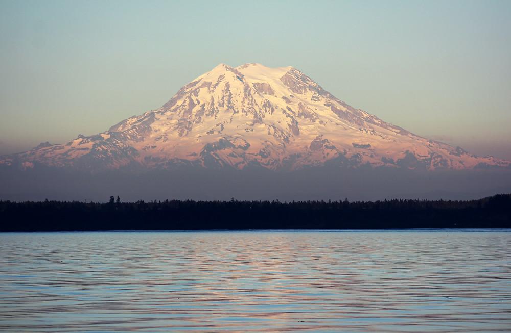 A sunlit mountain behind a lake