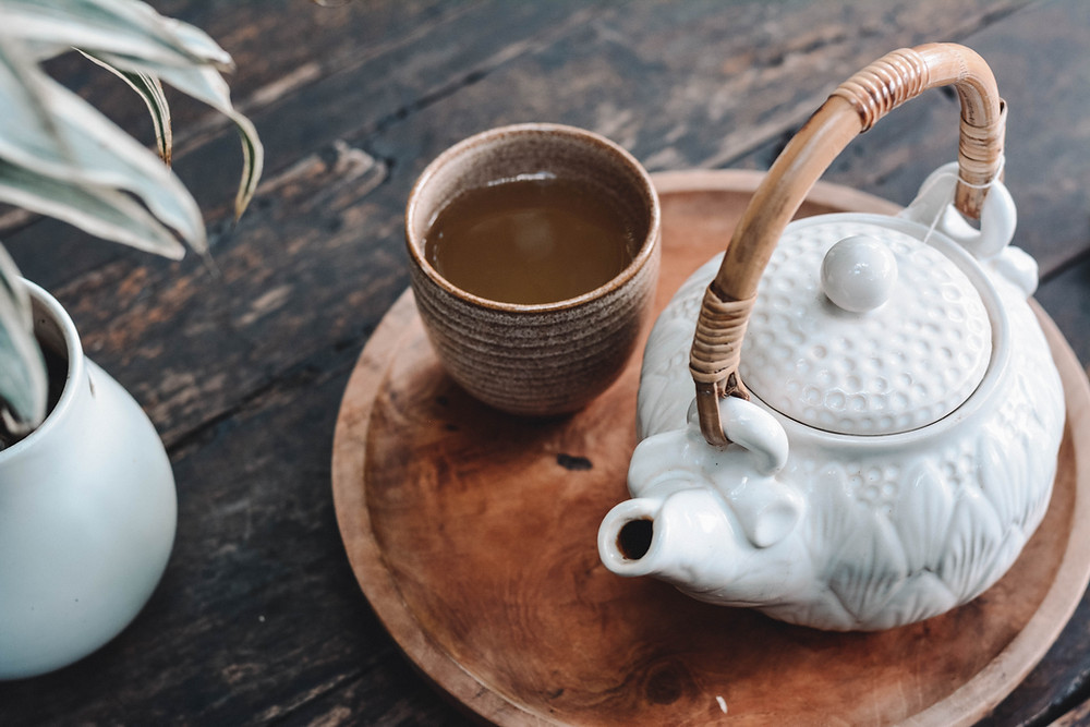 A white ceramic tea pot and a brown ceramic mug with tea resting on a table