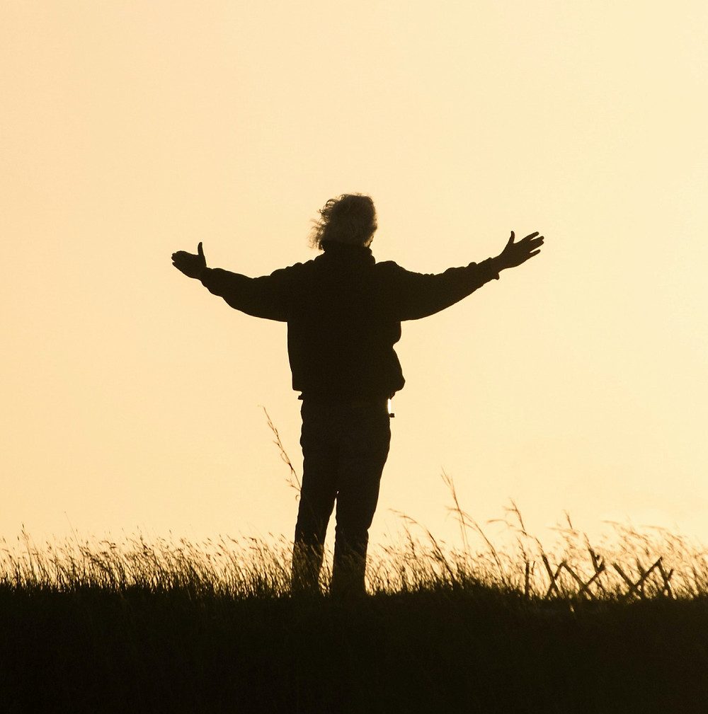 A person standing in a field with arms wide open