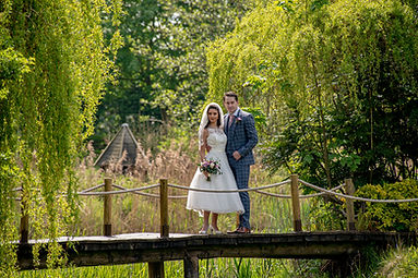 Bride and  groom  kissing under a canopy of trees
