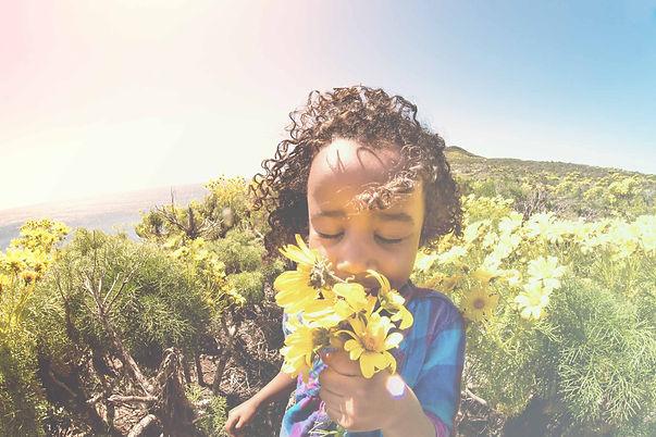 menina cheirando flor.jpg