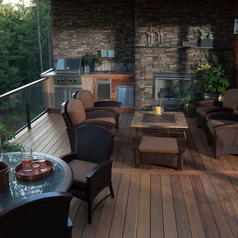 Teak deck with beautiful deck furniture outdoor kitchen and living space with fireplace.