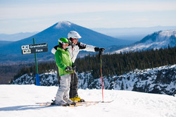 man-giving-directions-to-daughter-while-skiing
