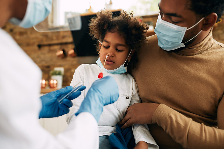 Small black girl sitting in father's lap while having PCR test at home. .jpg