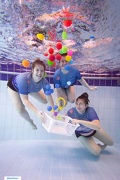 3 swimming instructors release a basket of colourful balls underwater