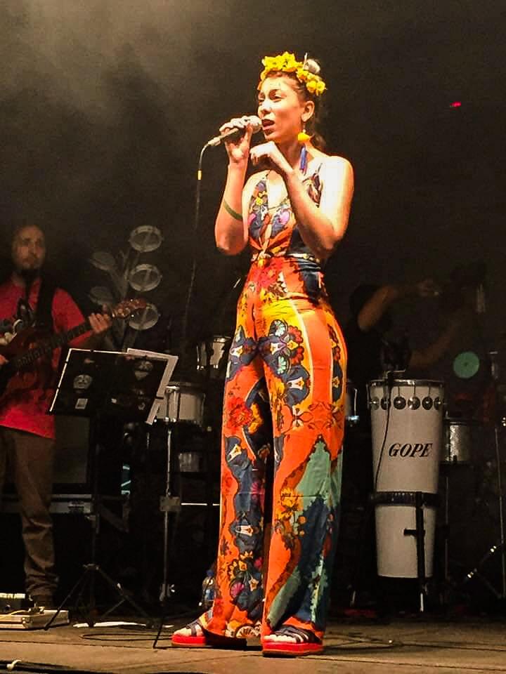 A artista Iraty Boelsums cantando em um palco, acompanhada de uma banda e utilizando uma roupa colorida.