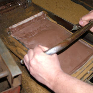 The tile maker trims any excess clay off the back of the tile.