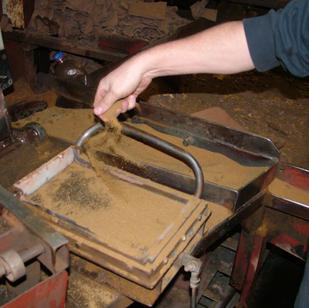 Before the clay is pressed into the mold the tile maker 'sands the box'. The sand will prevent the clay sticking to the box.
