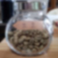 瓶に入ったコーヒーの生豆の写真
