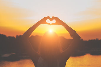 Person making heart hands at sunset | LGBTQ counseling near me | LGBTQIA counseling in Parkland, FL | LGBTQIA counseling in Coral Springs | LGBTQ therapists | LGBTQ couples counseling | 33334 | 33064 | 33433 | 33325 | 33432
