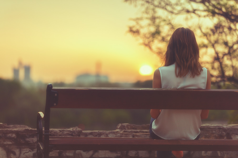 Woman Thinking about Ending her relationship sitting on a bench