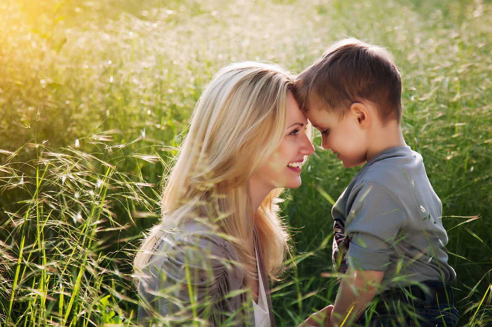Mother & Son Laughing together in a field | Being A Mother | Maternal Counseling | New Mom Counseling