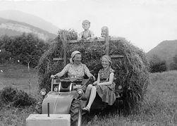 """Mutter mit dem ersten """"Motorfahrzeug"""" am Hof"""