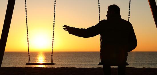 Man on a swing reaching toward an empty swing in a sunset