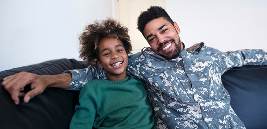 Military dad and sun smiling on a sofa