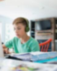 focused-boy-with-headphones-using-laptop
