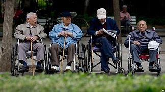 Four elderly men in wheelchairs