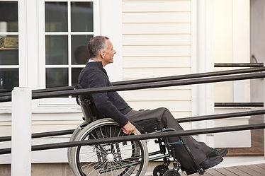 A man in a wheelchair going up a wheelchair ramp