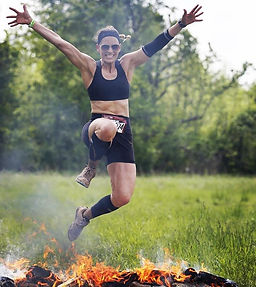 Photo of a woman jumping over fire surrounded by grass and trees with obstacle racing gear on.