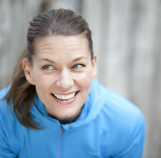 Headshot of a female trainer smiling, glancing sideways, leaning into camera.