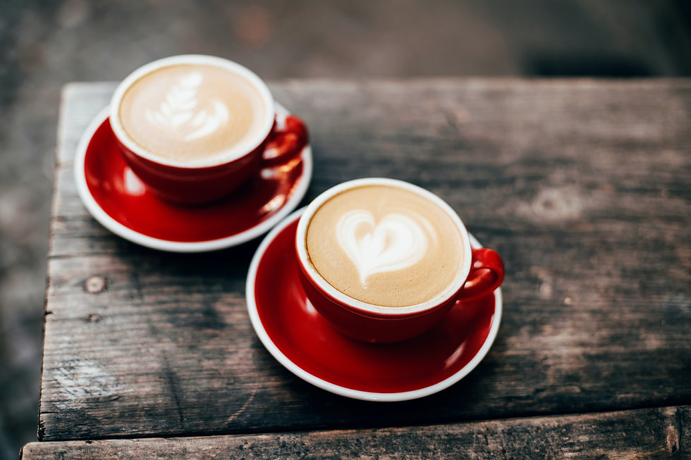 Two red cups of cappuccino with latte ar