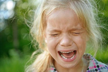 Beautiful sad little girl crying, on sum