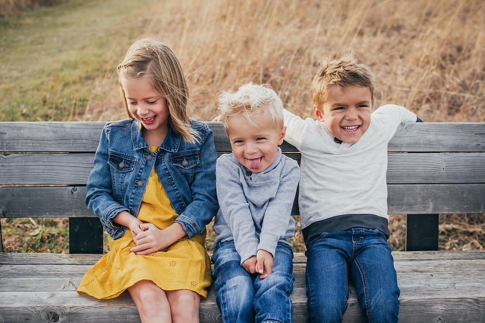 kids sitting on a park bench getting photo taken by Kara Joy Photography