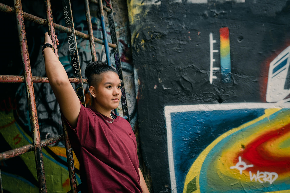 senior girl standing next to gated tunnel with her arm on the gate gazing outward and graffiti wall beside her