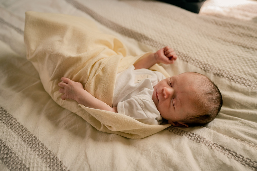 Minneapolis Newborn Photographer photographing baby in a swaddle blanket on a bed using natural light