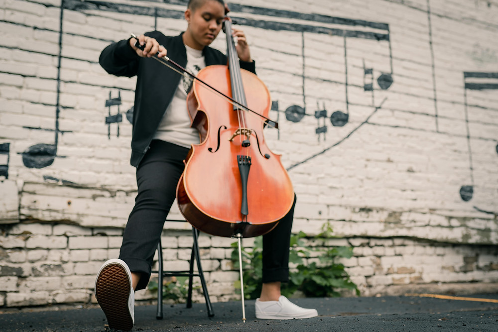 Senior girl playing the cello next to a brick wall of musical notes in downtown Minneapolis