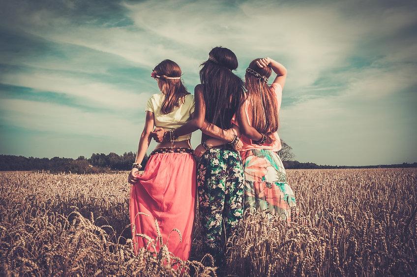 Multi-ethnic hippie girls  in a wheat fi