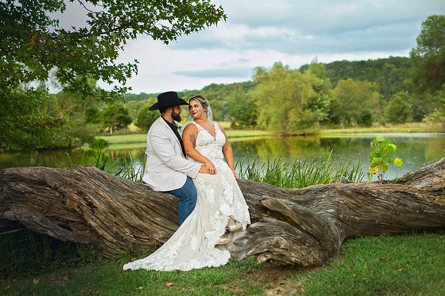 Bride and Groom sitting Lakeside at Wicked Pony Ranch
