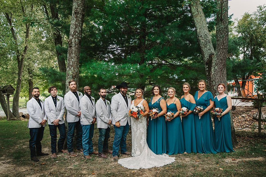 Wedding Party taking photos  on the wooded grounds before celebrating in the Rustic Reception Barn at Wicked Pony Ranch